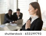 Small photo of Young beautiful businesswoman enjoys meditating standing in office with eyes closed, put hands together as in prayer, reduce stress, relief to keep calm, positive thinking, appeasement, autosuggestion