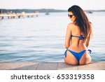 young woman sitting on a pier... | Shutterstock . vector #653319358
