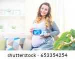 Pregnant Happy Woman Holding...