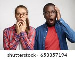 Small photo of Frightened two people with different races staring at camera with great surprise. Cute female with eyeglasses holding hands on mouth looking with amazement, dark-skinned male holding hand on head