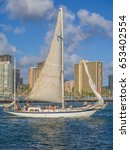 Small photo of Honolulu, Hawaii, USA, June 4, 2017: Classic yawl type of sailboat in Waikiki on a tropical evening with resorts in the background.