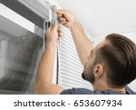 man installing window blinds at ... | Shutterstock . vector #653607934
