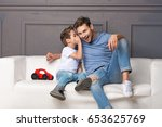 father and son are sitting on... | Shutterstock . vector #653625769