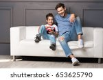 father and son are sitting on... | Shutterstock . vector #653625790