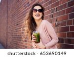 happy woman drinking spinach... | Shutterstock . vector #653690149