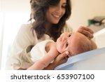 mother washing a newborn baby... | Shutterstock . vector #653907100