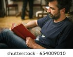 man reading book while sitting... | Shutterstock . vector #654009010