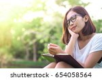 young woman sitting daydreaming ... | Shutterstock . vector #654058564