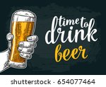 male hand holding a beer glass. ... | Shutterstock .eps vector #654077464