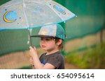 little boy under umbrella | Shutterstock . vector #654095614