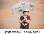 little boy under umbrella | Shutterstock . vector #654095890