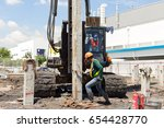 worker setting concrete pile to ... | Shutterstock . vector #654428770