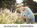 Stock photo senior woman smelling flowers in garden 654442804