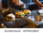 cook preparing burger adding... | Shutterstock . vector #654461863
