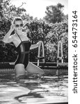 Small photo of Fun weekend alfresco. Portrait of smiling active woman in blue swimsuit in the swimming pool in sunglasses