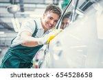 smiling man washing car   Shutterstock . vector #654528658