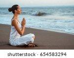 meditating woman on the beach | Shutterstock . vector #654583294