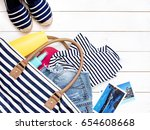 Small photo of Beach women's clothes and a bag on a white background. Denim shorts summer shoes Striped T-shirt Sunscreen Top view White background