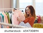 woman is choosing a dress in... | Shutterstock . vector #654730894