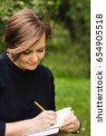 beautiful woman writes down in... | Shutterstock . vector #654905518