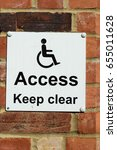 Small photo of Disabled access keep clear sign on white set against a brick wall