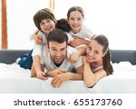 family of four lying on bed  | Shutterstock . vector #655173760