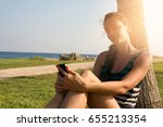 woman is leaning on palm tree... | Shutterstock . vector #655213354