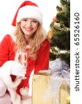 Cheerful santa girl sitting near the gift under New-year's tree with glass of champagne. Christmas greetings card - stock photo