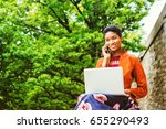 Small photo of Young African American Woman studying, working on laptop computer, talking on cell phone outside in New York, wearing orange red jacket, flower patterned skit, sitting by trees on campus, smiling.