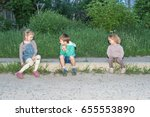 Children Sit On The Curb Near...