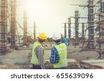 Two young man architect on a building construction site - stock photo