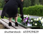 Woman Laying Flowers On A Grav...