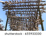 Small photo of Air-dried Cod stockfish hanging on the wooden rack and blue sky background at Moskenes, Lofoten Islands, Norway