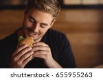 happy man eating burger in... | Shutterstock . vector #655955263