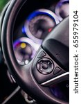 Small photo of Car Interior steering wheel drive hand pushes Cruise control buttons on modern car and speed limitation .