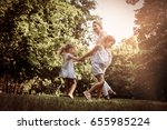 mother playing on meadow with... | Shutterstock . vector #655985224