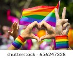 Small photo of Supporting hands make peace and heart signs in front of a rainbow flag flying on the sidelines of a summer gay pride parade