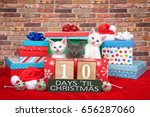 Stock photo two fluffy white and one gray kitten popping out of a pile of presents small santa hats toy mice 656287060