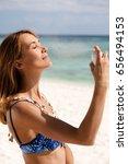 woman in bikini sprays her face ... | Shutterstock . vector #656494153