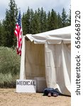 Small photo of Medical tent entrance with a hand-made medical sign and an American Flag. Could be a runners aid station, as indicated by the shoes outside of the entrance.