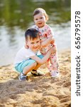 Small photo of The boy hugs his little sister. Brother and sister are walking in nature. Children smile