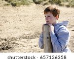 Young boy, leaning on a post and gazing into the distance at the beach. - stock photo