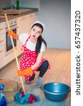 Small photo of Portrait of a young weary housekeeper who sits on the kitchen and washes the floor