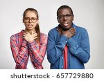 Small photo of Human emotions, feelings, reaction and attitude. Young interracial couple holding hands on throat as if suffocating, choking or having sore throat or expressing their disinterest and indifference