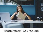 Small photo of Charming pensive employee of trading company receiving business letter with documentation sitting at working space with laptop computer,concentrate secretary assistant opening envelope with papers