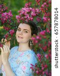 Small photo of The girl's portrait with green eyes in the blossoming apple-tree with claret flowers