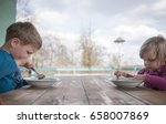 boy and girl eating soup at... | Shutterstock . vector #658007869