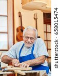 Small photo of Senior citizen as luthier master working with experience on new guitar
