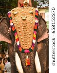 Small photo of Decorated Indian male elephant with gold plated caparison standing for parade on festival in Ernakulam temple for the traditional ceremony Kerala, India.