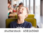 boy is laughing loudly in cafe | Shutterstock . vector #658165060